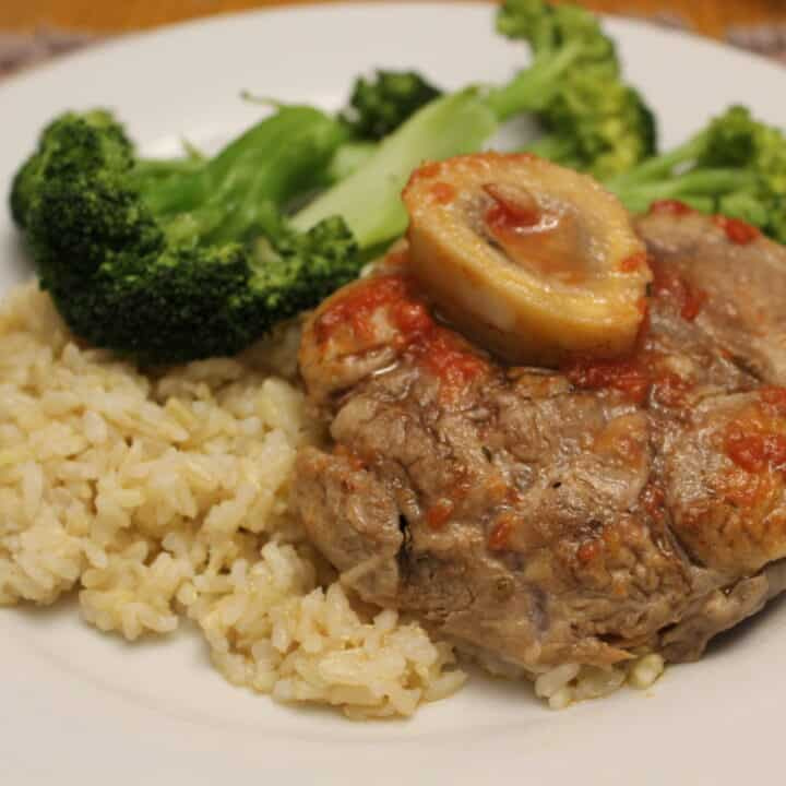 Osso Buco Veal Shank in a white plate with rice and broccoli