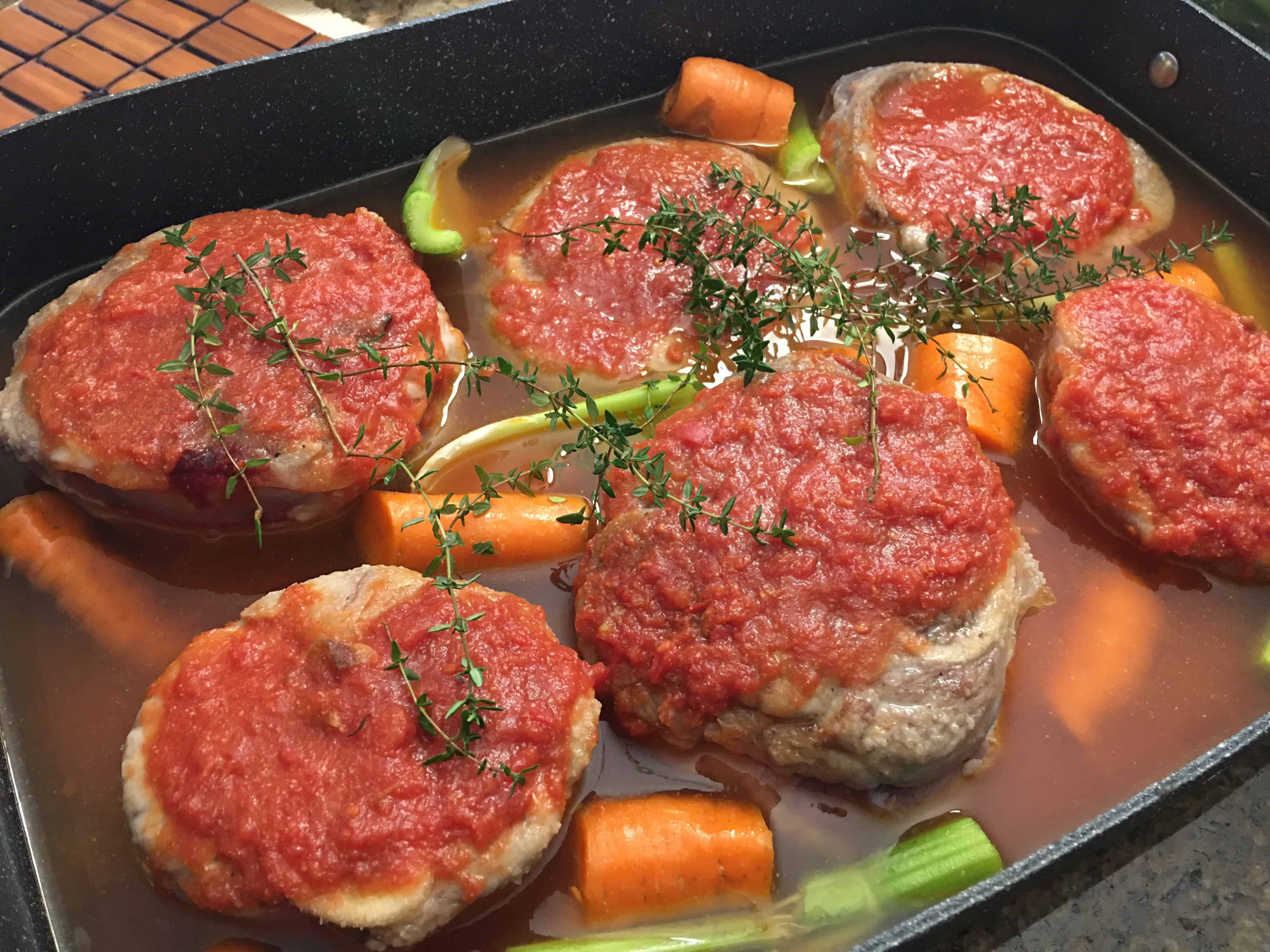 osso buco with sauce in a baking dish