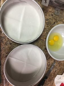 Three cake pans for 3 layer cake on a counter