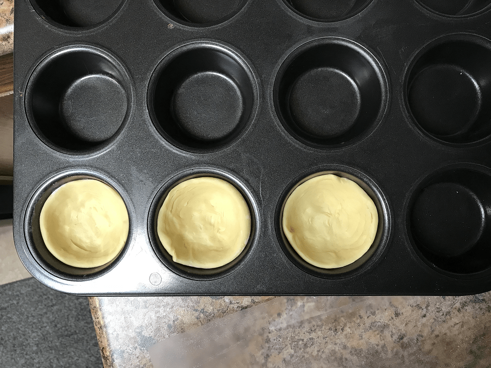Puff pastry dough pressed into a muffin tray