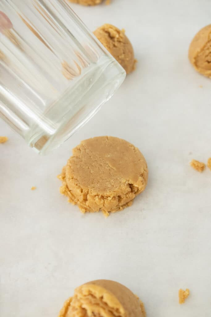 flattening cookie dough with a glass